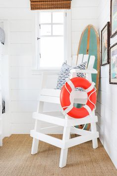 Cute nautical touch with life guard chair, surfboard and life preserver ring... for a bunk room. By Blackband Design.