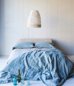 Bed on floor with blue hues.