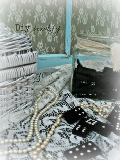 Set a gorgeous display with an old window, lace, a wicker suitcase, pearls and black dominoes