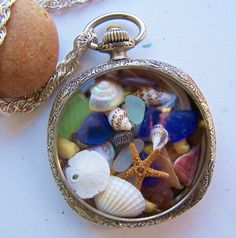 Vintage pocket watch case filled with sea glass, sea shells, starfish and sand dollar. Gorgeous pendant necklace on sterling silver chain. Stone Street Studio.