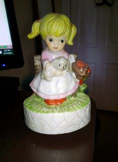 For sale is a wonderful music box that is a little girl holding a bunch of a cute little puppy.   She is sitting on a small bench with a basket of app