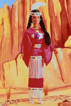 "This Native American doll, from the Southern Plains, is dressed in an updated version of a tribal princess costume. Pretty in a pink tunic and skirt with geometric patterns, her costume is trimmed in white fringe and ribbon. Her moccasins, beaded necklace, ""turquoise"" earrings and ring complete this modern powwow look."