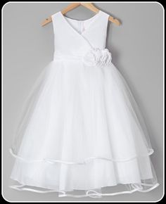 This inspirational white Communion formal dress boasts a gorgeous cross over satin bodice, satin waist band with removable flower pins and two layer t-length tulle skirt with satin trim hems.