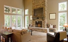 Light beige tones cover this high ceiling room, centered around a stone brick fireplace with wood mantle. Tall windows light the brown leather chair, tan couch, and dark wood coffee table.