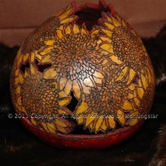 Sunflowers are the only flower which turns its face to the sun and follows it as it passes overhead during the day. Wherever there were corn fields, there were sunflowers also. Their seeds provided high nutrients during winter months. The gourd is wood burned and cut through giving a 3-D effect.