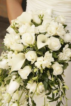 gorgeous bridal bouquet in a traditional all white cascade style. White calla lilies, white freesia, white roses, and white lisianthus with accents of pearl strands.