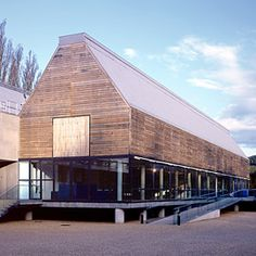 The design of this new museum draws both upon its boating theme and the forms of traditional local barn buildings. The effect of the oak-clad structure with its glazed ground floor is of a floating wooden boathall, raised on concrete stilts.  The uppermost structures are of steel, and form the two main galleries. These are clad with boards of English oak, cut downwards at the edges to help drainage and fastened with 23,000 stainless steel screws. The framework rests on a concrete table, ...