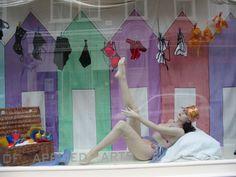 A Seaside window display with painted beach huts and Marlies Dekkers bikinis on the washing line.