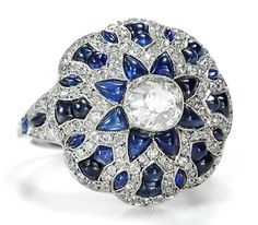 Diamond Sapphire Dome Ring This particular modern platinum example places its emphasis on the thirty-six (36) natural sapphires cleaved in a variety of shaped from triangular cabochons to cabs of exotic geometrics. Set about an estimated 90 point centered cut old European diamond (color K-L; VS2-SI1 clarity) the sapphires form a brilliant multi-petal flowerhead.    A lush courtyard of 124 old European cut accent diamonds (color J-L; VS1-SI1 clarity) cw 1.5 carats