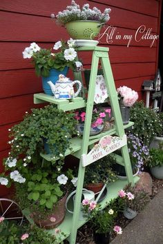Old wood ladder painted green with shelves for flower pots and garden art. Love the colander planter on the top!
