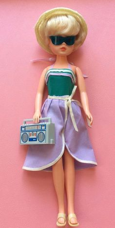 Sindy is in her original Jade green swimsuit with lilac and cream trim, lilac beach skirt with cream ties, straw sun hat, cream sandals and dark green sunglasses. She carries her original grey radio cassette player.