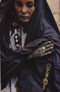 Algeria, August 1973 [source: vintage national geographic scans]    Hands gleaming darkly with the indigo dye that colours her robe, a woman of the Tuareg- wandering Berbers of the Sahara- clasps her traditions close. The incised brass key marks her as guardian of the family's saddlebags.