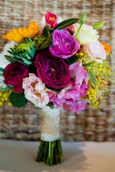 Bold spring hued bouquet in fuchsia, orange, green, pale pink & ivory | Country Couture Texas Wedding With Summer Camp Whimsy | Photography by Debra Gulbas Photography  Debra Gulbas Photography  http://www.storyboardwedding.com/romantic-country-couture-texas-wedding-summer-camp-whimsy/
