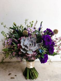 Beautiful deep violet blooms make this sprawling wedding bouquet complete with a large succulent centrepiece a real stunner // Pantone's Colour of the Year 2018 is Ultra Violet – a shade of purple that describes amethyst crystals and the swirling nebulae of the cosmos. With such a bold colour coming back in favour again, we just had to ask some of our florist friends to each create their unique takes on bouquets inspired by Ultra Violet, to show you how you can use this royal shade!