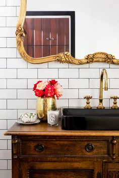 Glam bathroom with subway tile, a vintage gold mirror, and a traditional wood dresser