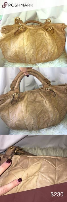 Miu miu hobo purse Beautiful miu miu hobo purse. Gently used, some normal wear and tear but still has lots of use left. See pictures...a few water stains but barely noticeable, slight cracking on handles( mink oil will help that) and a couple pen marks that are very slight. Going through my closet and I just don't use it that often or I would keep it. Reasonable offers please. Thank you! Miu Miu Bags Hobos