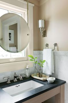 In the small bath, a mirror is suspended with metal rods in front of the window, allowing some sunlight to pass through. PHOTO: LAUREY W. GLENNThe Bunkie Bath