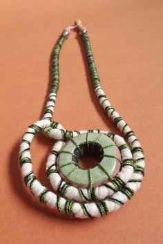Produzido com peças de cerâmica feito a mão,misturando corda ,linha e tecido, dando um aspecto rústico para o colar. <br>Ele pode ser usado dos 2 lados, pois o círculo de cerâmica tem 2 cores, verde e preto (observe na foto). <br>Comprimento do colar aberto aproximadamente(de ponta a ponta) = 64 cm <br>Peso= 51 g