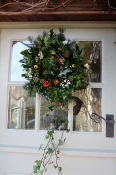 Homemade hedgerow wreath made with holly, ivy, rose hips, viburnum and twigs with catkins.