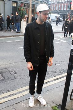 Men's street style, a monochrome look with an all black outfit featuring black skinny jeans, t-shirt and denim jacket, brightened up with white snapback and white shoes. | Shop men's clothing, shoes and accessories at The Idle Man