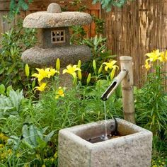 Amid lilies and moneywort, a Japanese-style garden with a concrete trough fountain adds trickling sounds to be heard on the dining deck. | Photo: Mark Lohman. | thisoldhouse.com