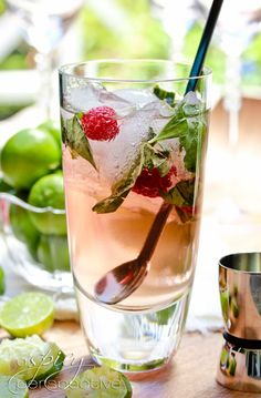 Raspberry Mojito - 1 cup simple syrup ( 3/4 cup sugar + 3/4 cup water, heated to dissolve),1/2 cup torn basil leaves, 1 cup FRESH lime juice, 2 cups white rum, 1/4 cup Chambord (raspberry liquor), 1 liter club soda      ice, fresh raspberries and lime slices to garnish