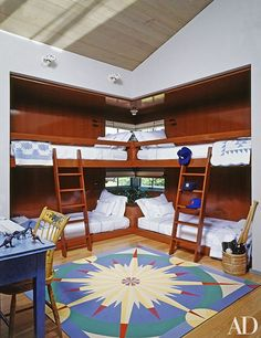 A children's bedroom in film director Steven Spielberg's East Hampton, New York, guesthouse, designed by architect Charles Gwathmey with interiors by Naomi Leff. Double bunk beds meet in the corner of the room, which is anchored by a colorful Matthew Imperiale rug next to a blue painted desk.