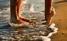 A menina eo indivíduo em pé em tippytoes na praia