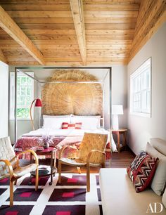 An exposed wood ceiling in a feminine bedroom with lounge area
