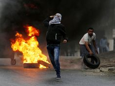 Palestinian protesters throw stones during clashes with Israeli soldiers in the West Bank village of Si'eer, north of Hebron, on Oct. 25, 2015. More than three weeks of unrest between Israelis and Palestinians has left more than 65 people dead. These include 57 Palestinians, eight Israelis and an Eritrean asylum seeker who was mistaken for an attacker and beaten to death by a mob in Israel.   Abed Al Hashlamoun, EPA