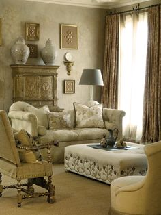 A blend of ivory, neutral and soft metallics create a polished sitting area. A plush cream sofa, tufted ottoman and gold armchair provide a variety of textures while still giving a harmonious blend of luxurious fabrics. A gold hutch paired with two ornate urns brings a touch of exotic charm to this space.