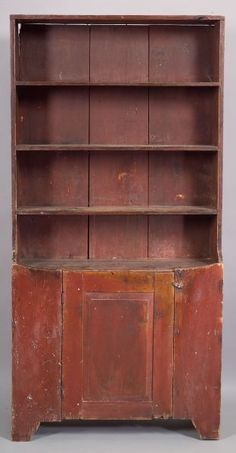 Painted Pine Paneled Cupboard, early 19th century, the four-shelved cupboard above the raised panel door which opens to a two-shelved interior above a front and side skirt, both with shaping, early red paint, (imperfections), ht. 79 1/2, wd. 39 1/2, 13 5/8 in.