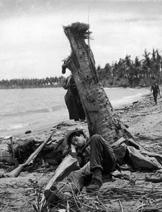 American soldier sleeping against a tree, after fierce fighting to take control of the area. Papua New Guinea, 1943.