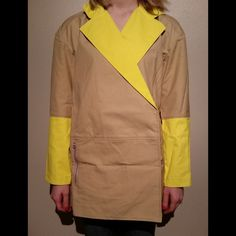 """🎉HPx2🎉tibi Bonded Rubberized Drop Shoulder Coat This coat is NWT! It is tan/khaki with rubberized yellow lining and bottom half of sleeves. It has 2 buttons for closure. Both buttons are hidden when closed. There are 2 zipper pockets in the front. It is approximately 21"""" across the bust when laid flat and buttoned and 28"""" from shoulder to hem. The sleeves are approximately 20"""" long. Shelf:  100% cotton     Lining:  51% acetate, 49"""" nylon Tibi Jackets & Coats"""