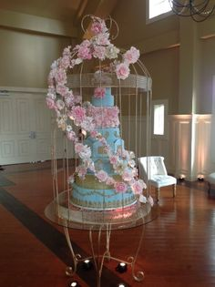 Beautiful cake in birdcage with adorning flowers by Crest Florist