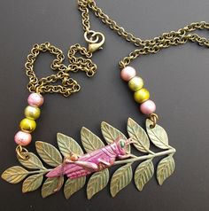 This unique necklace features a brass grasshopper that I hand painted in shades of pink and copper and brown. The grasshopper was then sealed.  I then