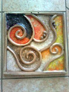 KACHEL VELKÝ-SPIRÁLY Masivní kachel z jemné šamotky,patinované oxidy,rozměr 31x31cm,dírky na připevnění,zavěšení...Sypané barevnými skly. Možno vyrobit tentýž ( spíše velmi podobný-co kus to origoš) motiv v barvách modravých...
