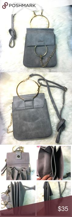 Stylish Crossbody Bag Metal hoop carry handle featuring detachable and adjustable shoulder strap.  Curb chain accent with lanyard clasp at side attached to ring feature at face. Fold over flap in grey tones with fastening. Patch pocket at interior. Grey lining.  Gold-tone hardware. Bags Crossbody Bags