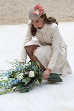 Catherine, Duchess of Cambridge places flowers at the Saint Symphorien Military Cemetery in Mons, Belgium