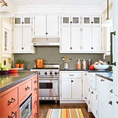 Open layout and cabinets of craftsman kitchen after remodel via This Old House. Upper cabinets with tin fronts,