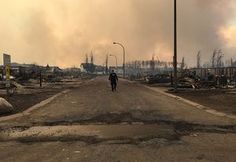 A police officer walks past burned-out houses in Fort McMurray, Canada