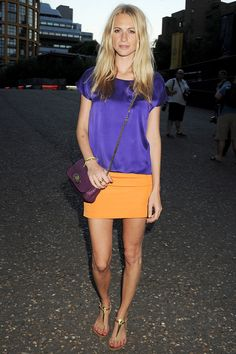 Poppy Delevigne in orange skirt and purple shirt and flat sandals - summer style