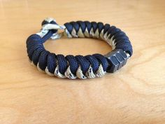 This listing is for a handsome two-tone black/desert camo snake woven paracord survival bracelet. Bracelet is beaded with black hex nuts and fastens