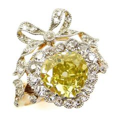 Belle Epoque yellow diamond heart cluster ring, c.1905, the pear shaped yellow diamond to a heart shaped border of white diamonds, tied ribbon diamond bow above, millegrain set in platinum and gold
