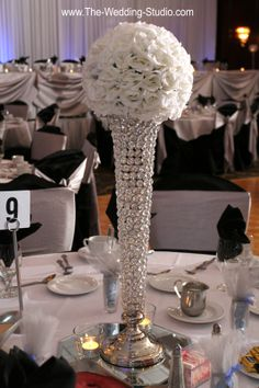 Eye catching center piece at the Mirage Banquets in Schiller Park. Lots of bling & sparkle! Tall vase appearing to be made with large crystals or rhinestones, topped with white flowers. Photographed by The Wedding Studio, Schaumburg IL