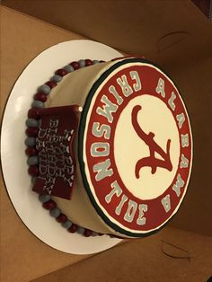 "Alabama Crimson Tide cake made with chocolate cake, vanilla buttercream, royal icing logo and fondant flag with birthday message and ""Roll Tide"" pennants"