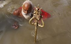 A devotee offers his prayers as he bathes at the banks of Sangam, in Allahabad