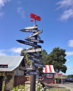 Directional sign showing the way to everything at the Vines Village, Blenheim, New Zealand. Retro triplane wind vane on top. More at www.thevinesvillage.co.nz #vinesvillage #purenewzealand #lovemarlborough