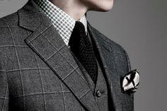 Plaid suit, checkered shirt, knit tie.