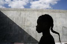 A 13-year-old girl stands in the yard of the women's prison in Haiti. Behind her stands a concrete wall, topped with barbed wire. Arrests of minors are frequently gang-related, with alleged offences ranging from petty crime to gun possession and assault.  Once in prison, they can be held indefinitely without being charged or tried. UNICEF provides sanitation kits and educational and art supplies to this prison - © UNICEF/NYHQ2005/Roger LeMoyne - http://www.unicef.org